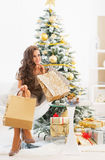Thoughtful young woman with shopping bags near christmas tree Royalty Free Stock Photo