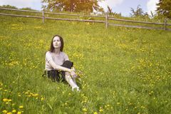 Thoughtful young woman sits on a flower meadow. Summer sunny day Royalty Free Stock Image