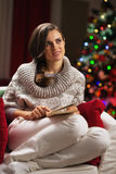 Thoughtful young woman sitting in armchair near christmas tree Royalty Free Stock Photography
