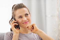 Thoughtful young woman sitting on couch and talking mobile phone Stock Image