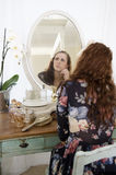 Thoughtful young woman sitting in front of mirror Royalty Free Stock Images