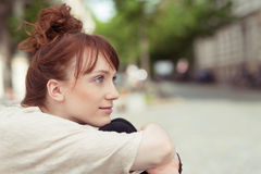 Thoughtful young woman sitting hugging her knees Royalty Free Stock Image