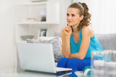 Thoughtful young woman sitting in living room and using laptop Stock Photography