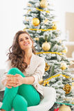 Thoughtful young woman sitting near christmas tree Royalty Free Stock Image