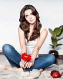 Thoughtful young woman sitting with red flower Royalty Free Stock Photography