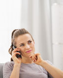 Thoughtful young woman sitting on sofa and talking cell phone Stock Image