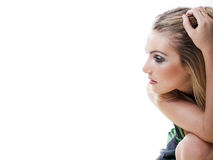 Thoughtful young woman. Sitting staring into space with her hand raised to her head, close up profile portrait on white to the right hand side of the frame with Stock Image