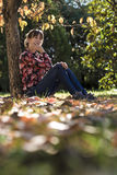 Thoughtful young woman sitting under an autumn khaki tree Stock Images