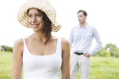 Thoughtful young woman smiling while man standing in background at park Stock Image