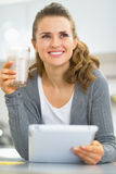 Thoughtful young woman with smoothie using tablet pc Royalty Free Stock Photography