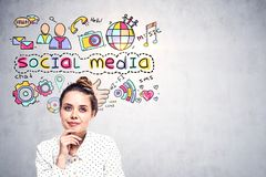 Thoughtful young woman, social media icons mock up. Thoughtful and inspired young woman in a dotted shirt sitting near a concrete wall wtih bright and colorful stock photos