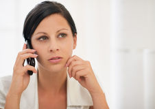 Thoughtful young woman speaking mobile phone. Thoughtful young woman in room speaking mobile phone Stock Image
