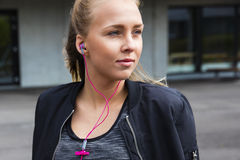 Thoughtful Young Woman In Sportswear Listening To Music Stock Photography