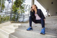 Thoughtful Young Woman In Sportswear Sitting On Steps Stock Images