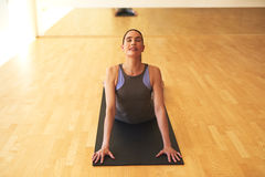 Thoughtful Young Woman Stretching on Yoga Mat Stock Photo