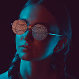 Thoughtful young woman in stylish round sunglasses stock photography