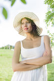 Thoughtful young woman in sundress and hat standing arms crossed in park Royalty Free Stock Images