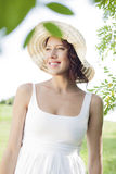 Thoughtful young woman in sundress and hat standing in park Stock Photos