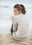 Thoughtful young woman in sweater sitting on lonely beach Royalty Free Stock Photography