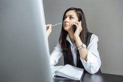 Thoughtful young woman talking on the phone in the office. stock image