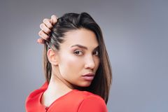 Thoughtful young woman turning back while touching her hair stock photography