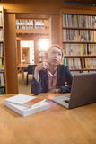 Thoughtful young woman using laptop in library. At college Stock Image
