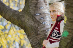 Thoughtful young woman in warm clothing standing near trees in park Stock Photos