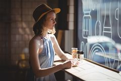 Thoughtful young woman wearing hat looking through window stock image