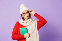 Thoughtful young woman wearing winter hat isolated over purple background reading book. Portrait of a thoughtful young woman wearing winter hat isolated over stock photos