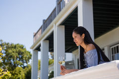 Thoughtful young woman with white wine glass standing in balcony at restaurant Royalty Free Stock Photography