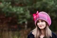 Thoughtful young woman in woolen cap. In garden Stock Image