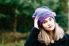 Thoughtful young woman in woolen grey cap Royalty Free Stock Images