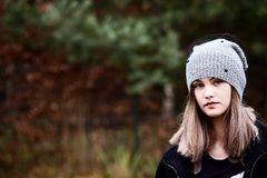 Thoughtful young woman in woolen grey cap Stock Photo