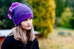 Thoughtful young woman in woolen violet blue cap Stock Images