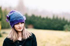 Thoughtful young woman in woolen violet blue cap Royalty Free Stock Photography