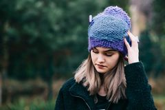 Thoughtful young woman in woolen violet blue cap Royalty Free Stock Photos