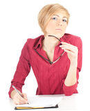 Thoughtful young woman writing on black clipboard Stock Photo