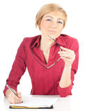 Thoughtful young woman writing on black clipboard Royalty Free Stock Photo