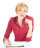 Thoughtful young woman writing on clipboard Stock Images