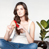 Thoughtfulcasual brunette girl holding red flower Stock Photo