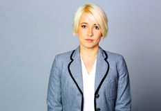 Thoughtfull businesswoman in gray jacket standing Royalty Free Stock Image