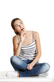 Thoughtfull female teen sitting on a table. Stock Images