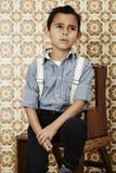 Thoughtfull pojke i hänglsen Royaltyfria Bilder