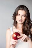 Thoughtfull young casual caucasian girl with red a. Natural light portrait young attractive casual caucasian girl with red apple on gray background stock images