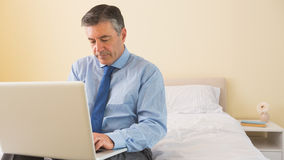 Thoughtfulman using a laptop sitting on a bed Royalty Free Stock Photos