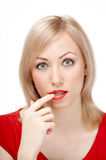 Thoughtfulness. The attractive woman in red has reflected on something, having brought a finger to a mouth, on a white background Royalty Free Stock Photography