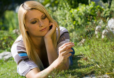 Thoughts. Young woman lying on the grass with her thoughts Royalty Free Stock Photography