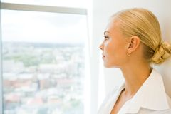 Thoughts. Image of pensive businesswoman looking through window in office Royalty Free Stock Photo