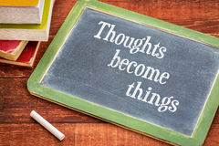 Thoughts become things - phrase on blackboard Stock Photos