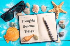 Thoughts become things text in notebook with Few Marine Items. Thoughts become things text in notebook with Beach Accessories and Few Marine Items On Blue Wooden stock photo